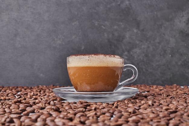 Uma xícara de cappuccino com feijão arábica ao redor.