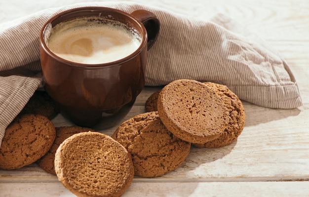 Uma xícara de cappuccino de café aromático com biscoitos de aveia.