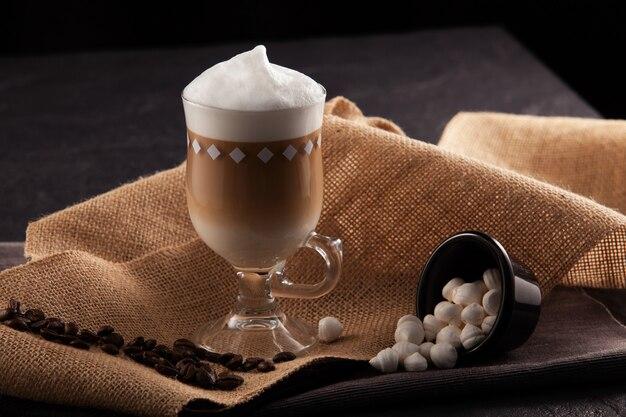 Uma xícara de cappuccino de vidro transparente com espuma alta
