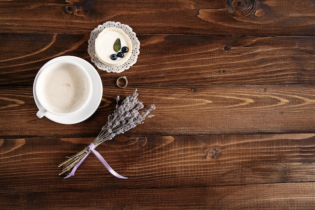 Uma xícara de cappuccino perfumado, bolo de mirtilo e um ramo de lavanda