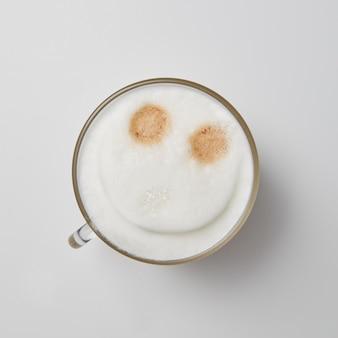 Uma xícara de cappuccino perfumado com um rosto sorridente em um fundo cinza com uma cópia do espaço. topo