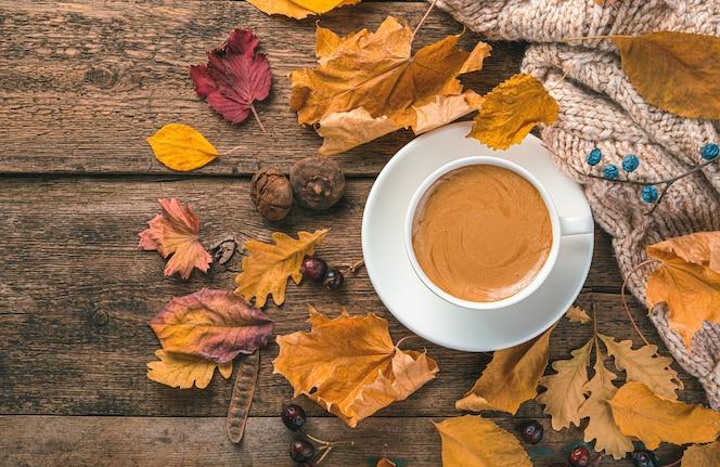 Uma xícara de cappuccino, um suéter e folhagem de outono em um fundo de madeira.