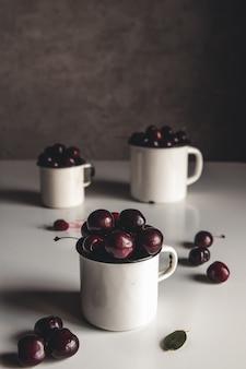 Uma xícara de cerejas em um fundo de concreto. produto ecológico orgânico, fazenda. sem ogm