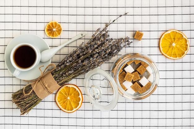 Uma xícara de chá, açúcar, limão e um buquê de lavanda em uma toalha de mesa quadriculada