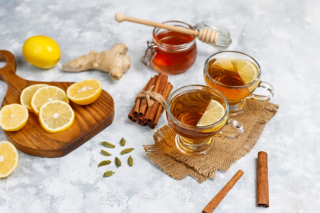 Uma xícara de chá, açúcar mascavo, mel e limão no concreto. vista superior, espaço de cópia