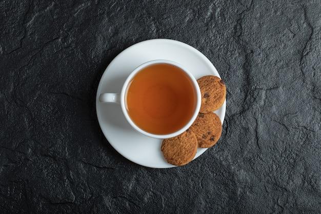 Uma xícara de chá aroma com biscoitos deliciosos.