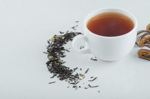 Uma xícara de chá aroma com chás soltos secos.