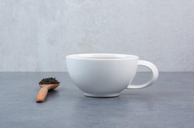 Uma xícara de chá aroma com uma colher de madeira de infusão.