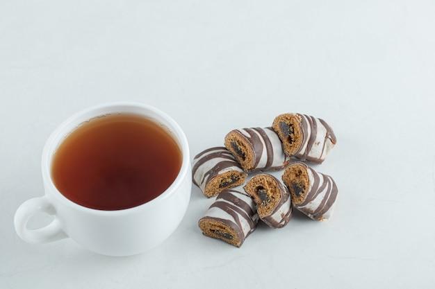 Uma xícara de chá aromático com barras de chocolate.