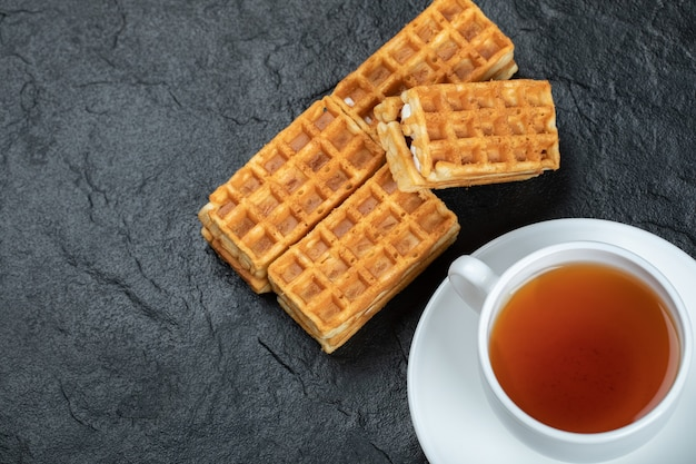 Uma xícara de chá aromático com deliciosos waffles.