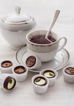 Uma xícara de chá branco com uma colher de chá e chocolate.