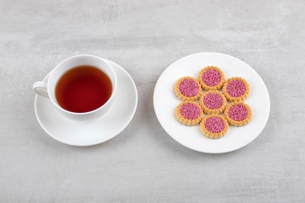 Uma xícara de chá com biscoitos, na mesa de mármore.