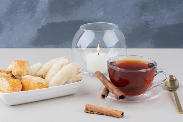 Uma xícara de chá com canela e biscoitos diversos na superfície branca.