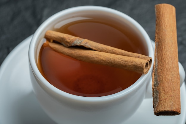 Uma xícara de chá com canela em pau e infusão.