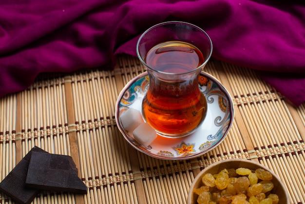 Uma xícara de chá com chocolate preto escuro e passas