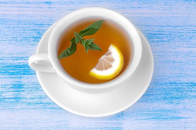 Uma xícara de chá com hortelã e limão em um fundo azul de madeira