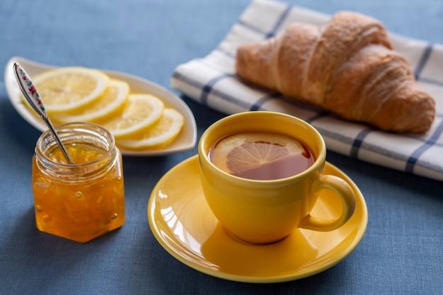Uma xícara de chá com limão, croissant, geléia, rodelas de limão em cima da mesa. café da manhã