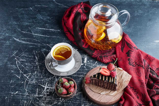Uma xícara de chá com limão e bolo de chocolate.
