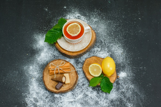 Uma xícara de chá com limão, folhas, canela seca em fatias de madeira e vista escura e superior.