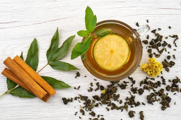 Uma xícara de chá com limão, hortelã e canela no branco, chá de sobremesa doce