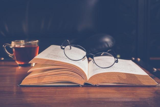 Uma xícara de chá com livro e óculos de leitura