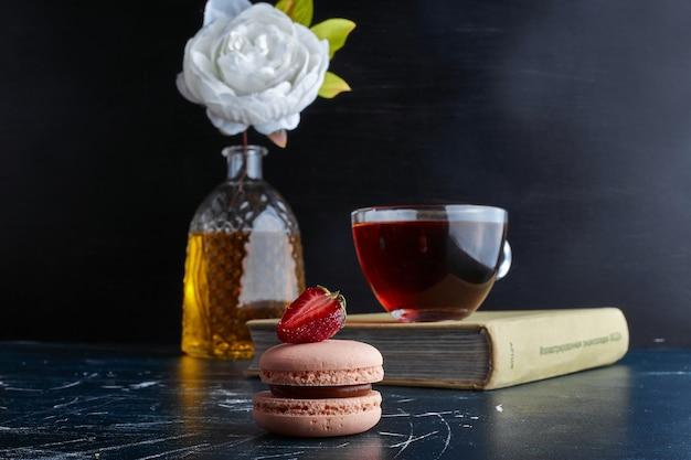 Uma xícara de chá com macaron rosa.