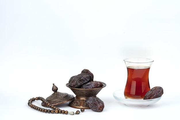 Uma xícara de chá com tâmaras em um prato isolado