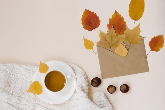 Uma xícara de chá com um pires, folhas secas de outono brilhantes, envelope kraft, castanhas, manta de malha branca sobre uma vista superior do fundo bege claro