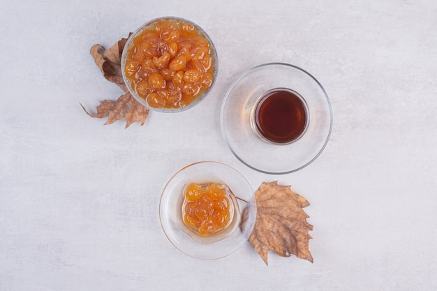 Uma xícara de chá com um prato de vidro com geleia na superfície branca
