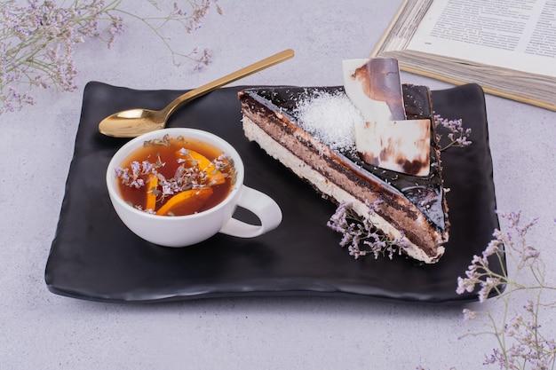 Uma xícara de chá com uma fatia de bolo de chocolate na superfície cinza