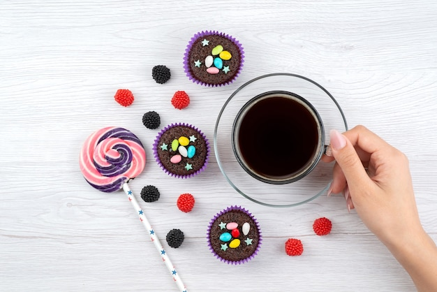 Uma xícara de chá com vista de cima junto com pirulito e doces em branco, beba cor de doce