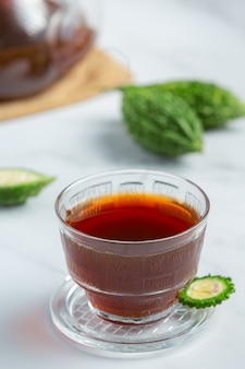 Uma xícara de chá de cabaça amarga quente com cabaça amarga fatiada crua no chão de mármore branco