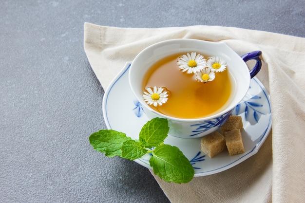 Uma xícara de chá de camomila com cubos de açúcar, deixa a vista de alto ângulo em um pano