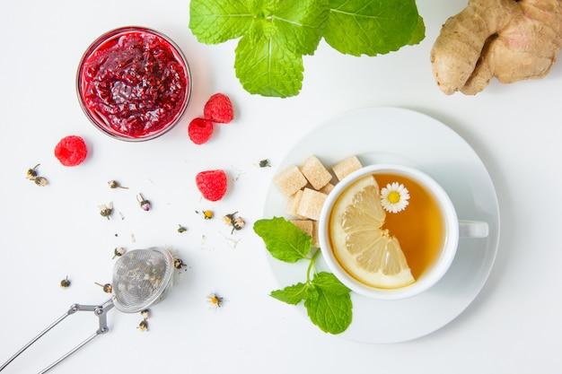 Uma xícara de chá de camomila com ervas, framboesas e geléia, folhas de hortelã, açúcar na superfície branca, vista superior.