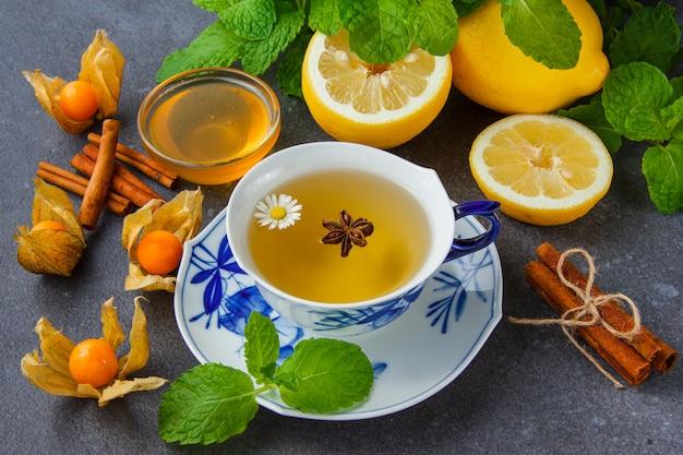 Uma xícara de chá de camomila com folhas de hortelã, limão, mel, canela seca, vista de alto ângulo