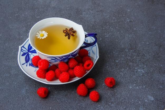 Uma xícara de chá de camomila com framboesa em pires