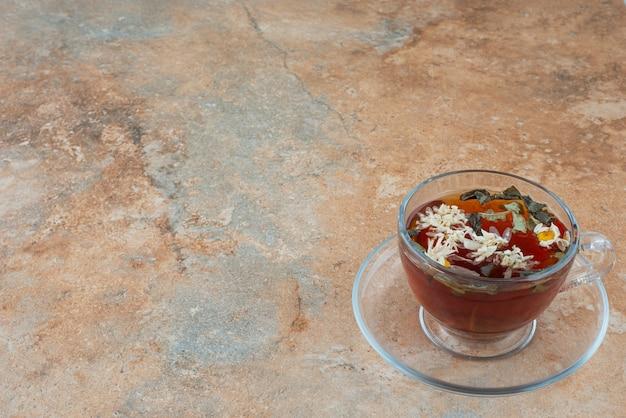 Uma xícara de chá de ervas aromáticas em fundo de mármore