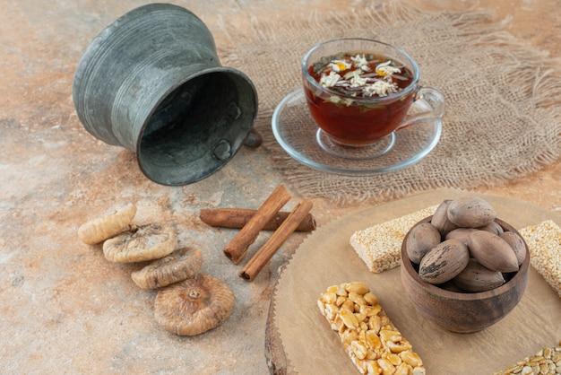 Uma xícara de chá de ervas com uma chaleira antiga e pedaços de amendoim