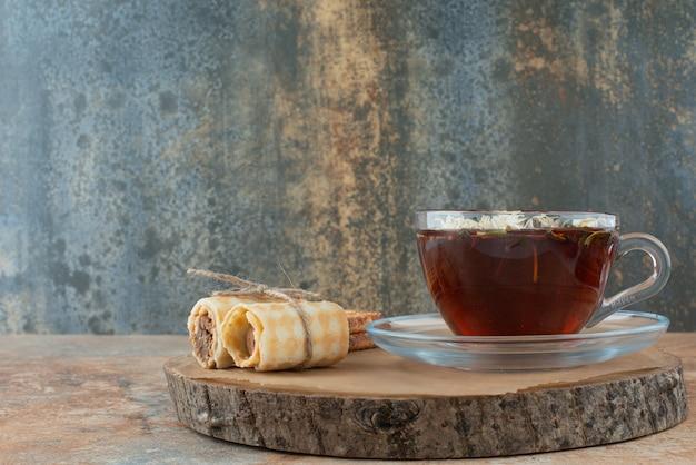 Uma xícara de chá de ervas com waffles na placa de madeira