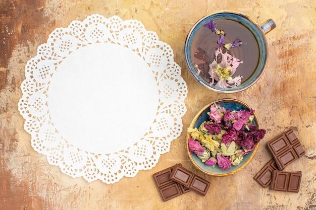 Uma xícara de chá de ervas quentes com flores, barras de chocolate e guardanapo no chá de mesa de cores misturadas