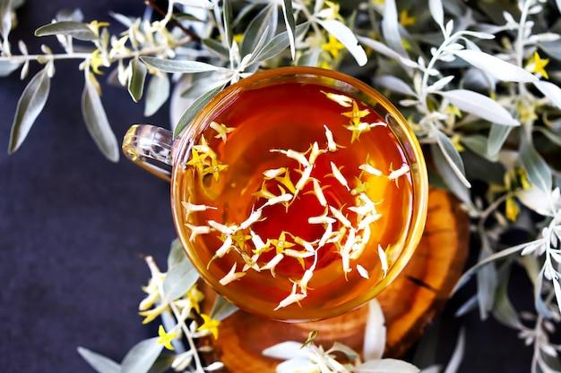 Uma xícara de chá de espinheiro. flores de espinheiro no chá. chá com espinheiro mar folhas. jovens ramos e flores de espinheiro. bebida curativa.