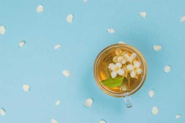 Uma xícara de chá de jasmim sobre um fundo azul com pétalas. uma bebida revigorante que faz bem à saúde.