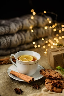 Uma xícara de chá de limão com foco seletivo na mesa com canela, caixa de presente e festão. noite aconchegante de inverno.