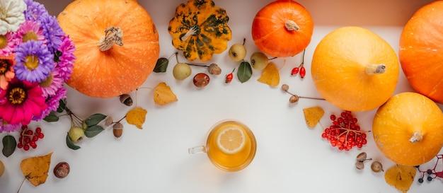Uma xícara de chá de limão em ação de graças de fundo de abóbora de outono e banner de halloween