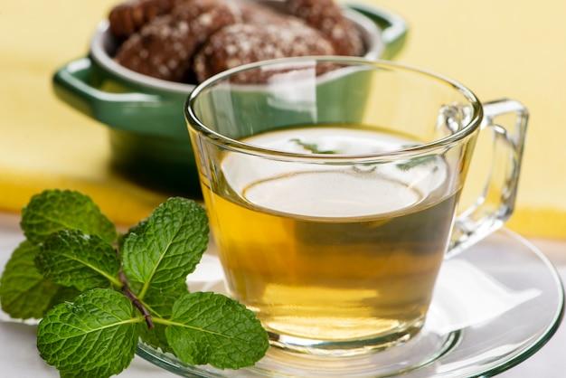 Uma xícara de chá de menta com alguns biscoitos doces