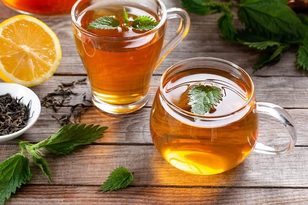Uma xícara de chá de urtiga em uma mesa de madeira, com urtigas frescas no fundo