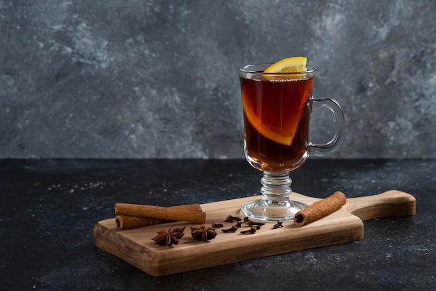 Uma xícara de chá de vidro e com paus de canela e anis estrelado.