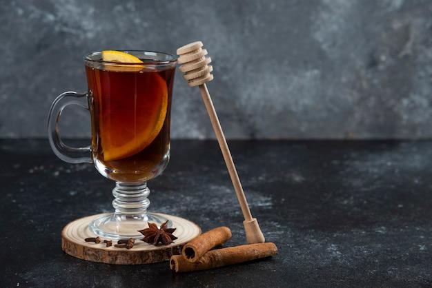 Uma xícara de chá de vidro e com paus de canela e concha de madeira.