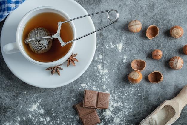 Uma xícara de chá delicioso com anis estrelado na chapa branca.