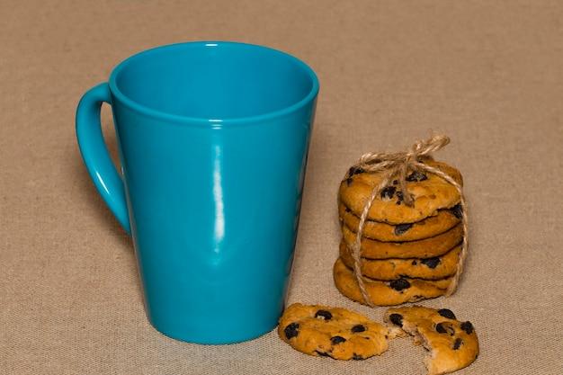 Uma xícara de chá e biscoitos na serapilheira de fundo.